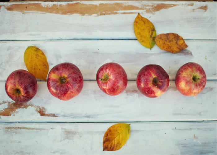 Aerial view of a line of red apples on a whitewashed wooden counter next to some yellow leaves