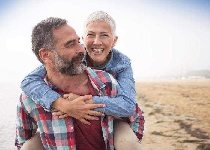 Aging husband and wife with graying hair smile as the husband gives his wife a piggy back ride on the beach