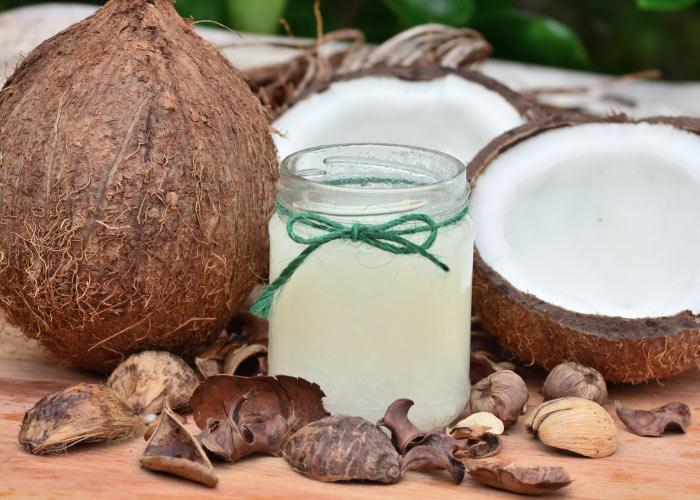 A jar of white coconut oil with a green string tied in a bow next to a cluster of coconuts, with a few cut in half