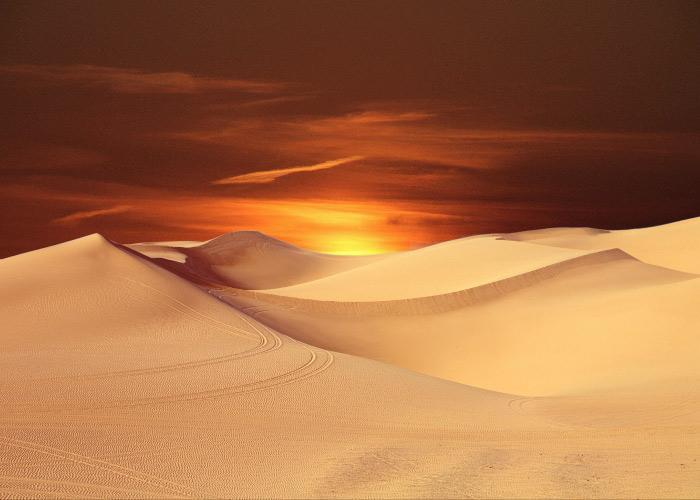 Dry desert landscape with tan sand and a vivid orange and yellow sunset, reminiscent of dry mouth