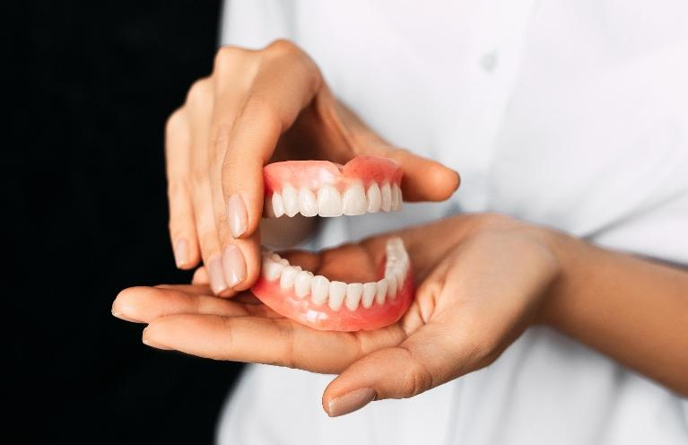 A woman holds dentures in her hands to discuss how dentures can improve a patient's overall health