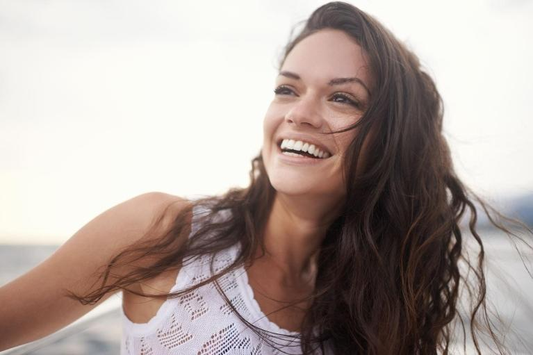 Brunette woman smiles after professional teeth whitening in Fredericksburg VA